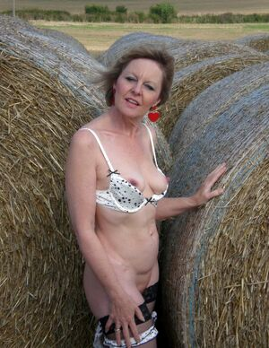 Beautiful smiley MILF photographed naked in the village