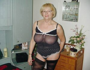 Sexpot mature ladies posing at home in stockings and fishnet lingerie.
