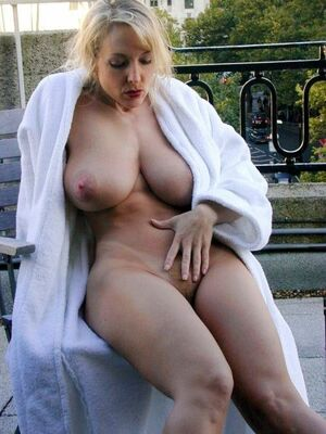 Blonde MILF with huge boobs posing naked outdoor
